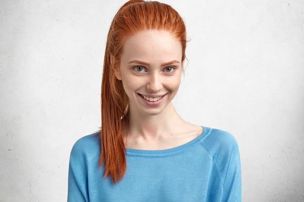 쾌활한 표정으로 행복한 젊은 여성 모델의 가로 세로는 캐주얼 한 옷을 입고 빨간색 밝은 조랑말 꼬리를 가지고 있으며 즐겁게 미소 짓고 남성으로부터 칭찬을 받기를 기뻐합니다.