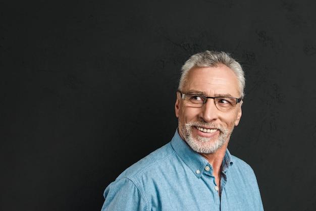 灰色の髪の眼鏡笑顔と黒の壁に分離されたcopyspaceをよそ見で成熟した剃っていない男60年代の水平方向の肖像画
