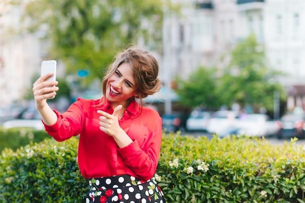 Горизонтальный портрет красивой девушки, стоящей в парке. она носит красную блузку и красивую прическу. делает автопортрет на телефоне.