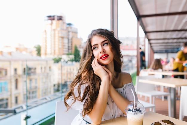 カフェのテラスのテーブルで長い髪シッティングとかわいい女の子の水平方向の肖像画。彼女は裸の肩と赤い口紅の白いドレスを着ています。彼女は側を見ています。