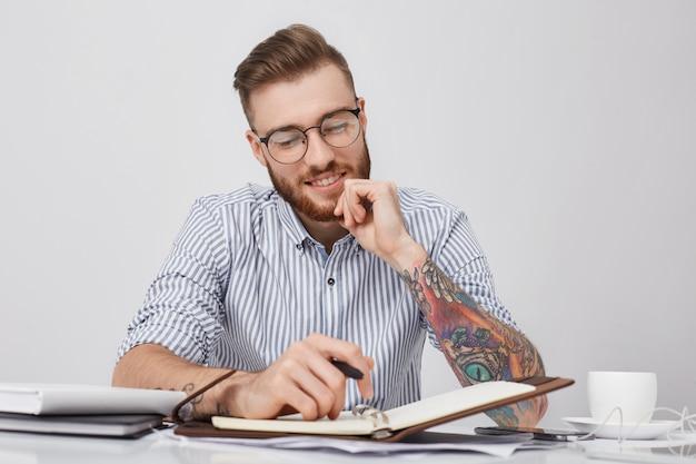 Горизонтальный портрет стильного татуированного бизнесмена с улыбкой смотрит в дневник, радуясь, что у него много свободных дней
