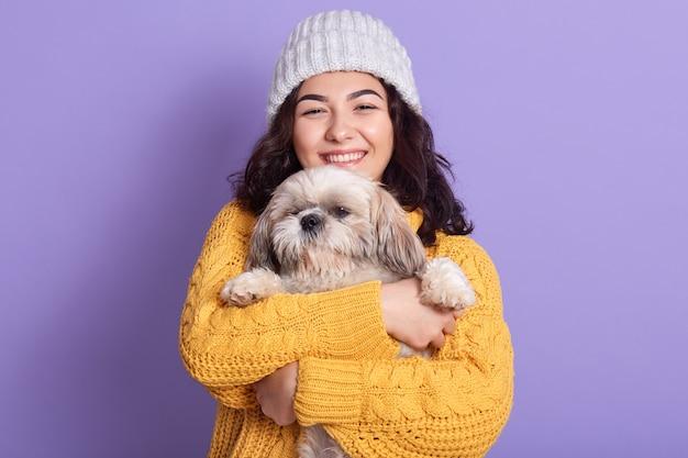 彼女の犬を手で保持している柔らかいかわいい若い女の子の水平方向の肖像画