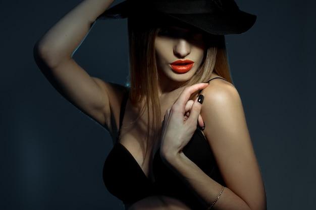 Горизонтальный портрет молодой красивой женщины в черном бюстгальтере и красных губах в шляпе с широкими полями
