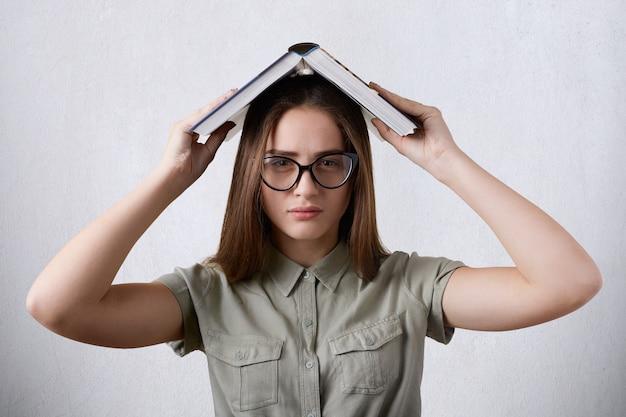 眼鏡と勉強に疲れている頭の上の本を持ってシャツを着ている若い女子学生の水平方向の肖像画。
