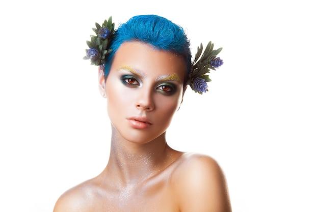 머리 스튜디오에서 파란색 헤어스타일과 꽃을 가진 어린 소녀의 수평 초상화는 격리되어 있습니다.