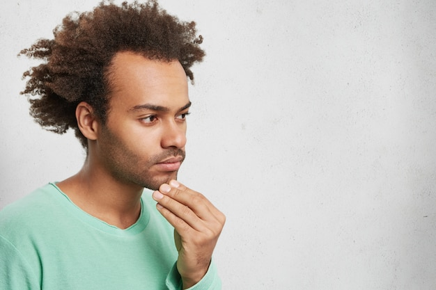 Horizontal portrait of pensive mixed race man with afro hairstyle, keeps hand on chin