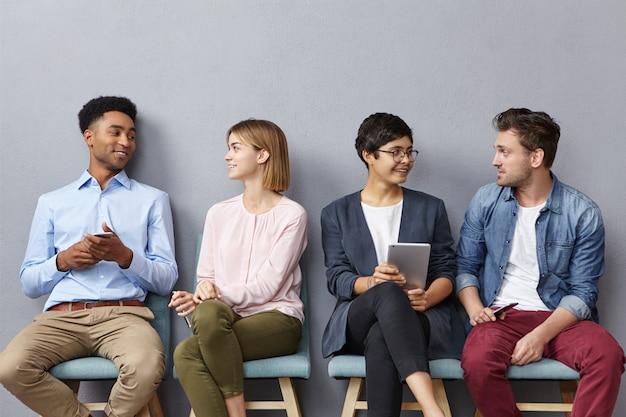 Ritratto orizzontale di persone sedute in coda, conversare piacevolmente tra loro,