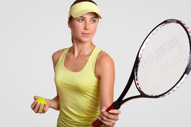 Horizontal portrait of pretty professional female tennis player holds racquet, ready to make favourite shot, holds ball