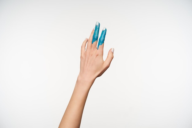 Horizontal portrait of pretty young lady's hand being painted in blue colour while raising it upwards, posing on white. body language concept