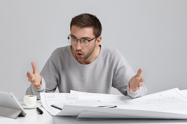 Horizontal portrait of puzzled male designer stares at screen of laptop