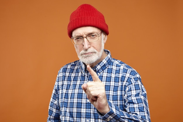 Horizontal portrait of serious strict old retired european man in stylish red hat, spectacles and checkered shirt