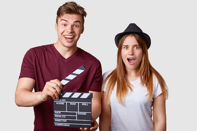 Horizontal portrait of shocked young successful female actress and her producer holds clapperboard, has cheerful expression