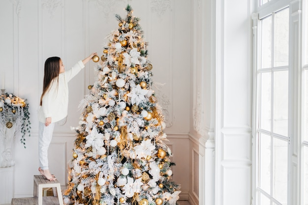 Horizontal portrait of small female child stands on chair, decorates christmas tree, tries to show best, being at home, enjoys domestic calm atmosphere, wants to satisfy parents, being hard working