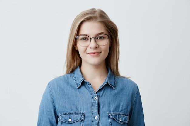 Horizontal portrait of smiling happy young pleasant looking female wears denim shirt and stylish glasses, with straight blonde hair, expresses positiveness, poses