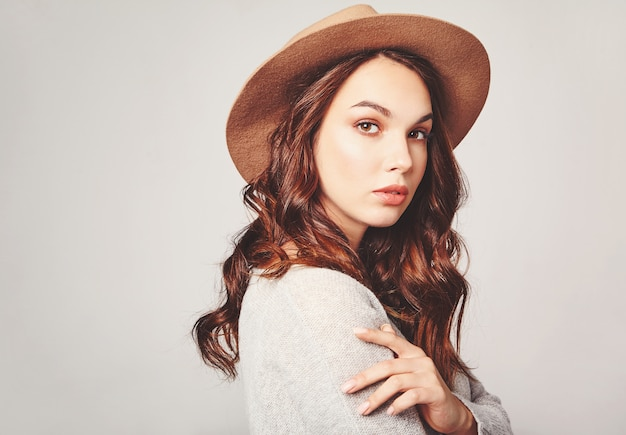 Horizontal portrait of stylish attractive female model wears summer clothes and brown hat with natural makeup