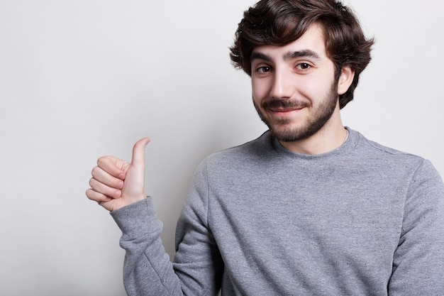 A horizontal portrait of stylish bearded hipster with trendy hairstyle being positive dressed in casual gray sweater raising his thumb showing ok sign. man showing his satisfaction.