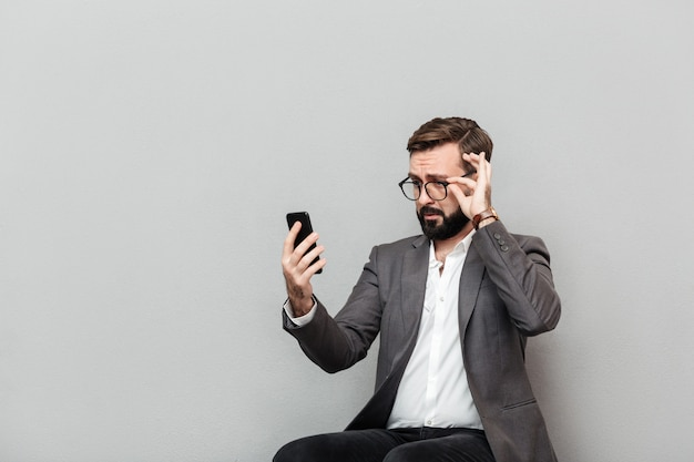 Horizontal portrait of stylish businessman looking at smartphone touching eyeglasses while sitting on chair in office, isolated over gray