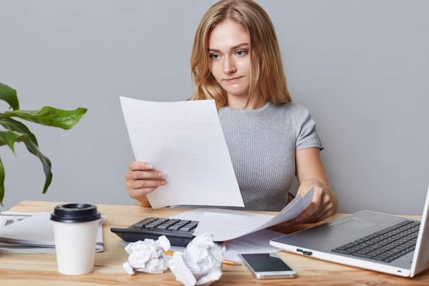 Horizontal portrait of successful businesswoman reads attentively business papers