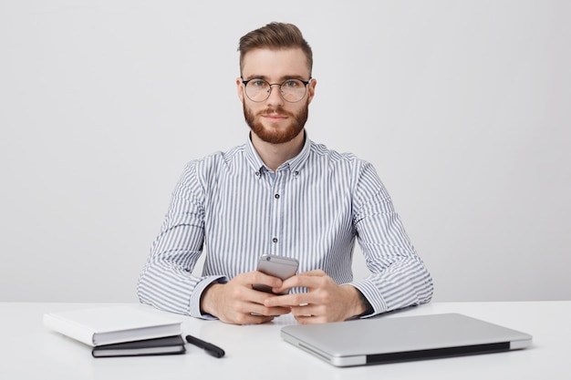 Horizontal portrait of unshaven pleasant looking young businessman sits at working desk,