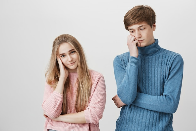 Horizontal portrait of upset couple in knitted colourful sweaters having some troubles in their family