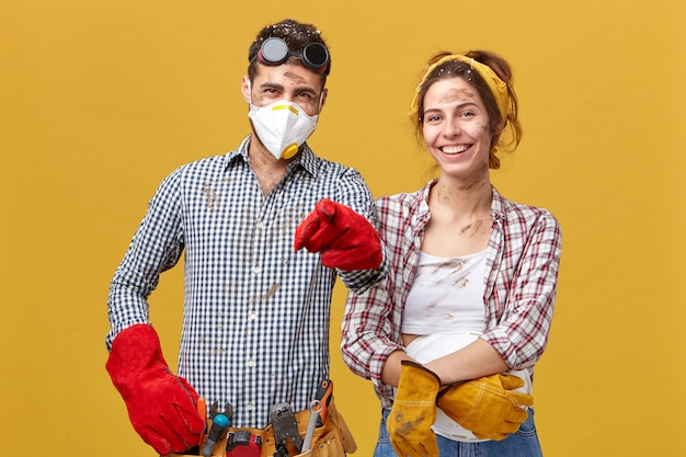 Horizontal portrait of young foreman wearing safety eyewear, mask and red gloves holding tool belt pointing with finger standing near her female colleague having smiles on their faces
