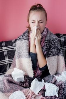 Горизонтальный портрет молодой девушки с носовым платком и насморком в профиль, чихание от гриппа, белая кожа женская модель на розовой стене. здравоохранение и медицинская концепция.