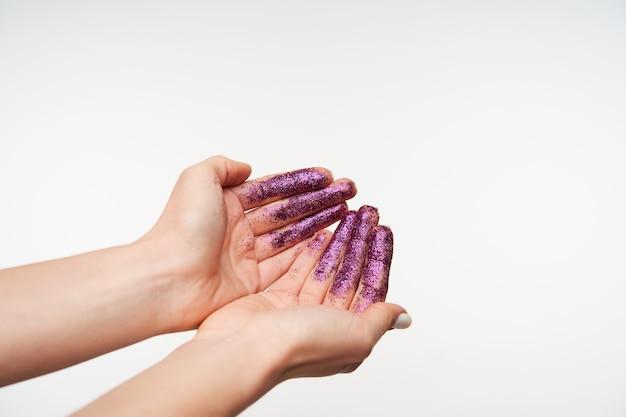 Ritratto orizzontale delle mani della giovane femmina graziosa che formano insieme mentre va a lavarsi le mani con acqua, essendo isolato su bianco
