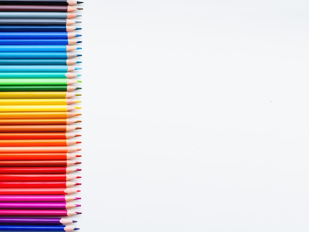 Horizontal row of colorful pencils on white background