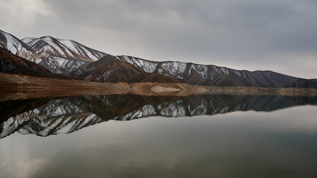 Horizontal scenic shot of a mountain range reflected on the waters of azat reservoir in armenia