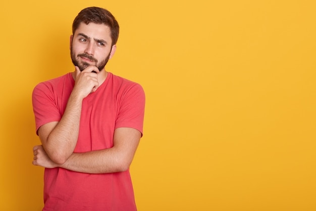 Horizontal serious unshaven male dresses casual red t shirt, keeps hand under chin, looks aside with serious facial expression, thinks about something, poses on yellow wall with free space.