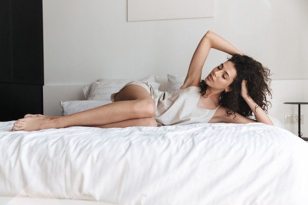 Horizontal sexual young woman with long curly hair wearing silk leisure clothing lying in bed at home, and propping up her head with hand