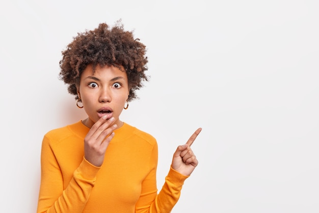 Horizontal shocked speechless woman with afro hair keeps jaw dropped indicates away on blank space says check out something unusual wears long sleeved orange jumper isolated over white wall