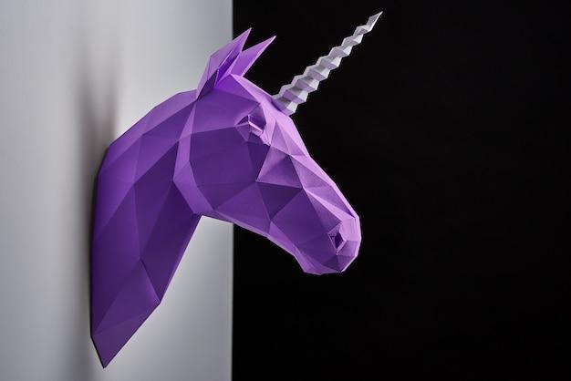 Горизонтальная стрела головы фиолетового единорога висит на серой тенистой стене.