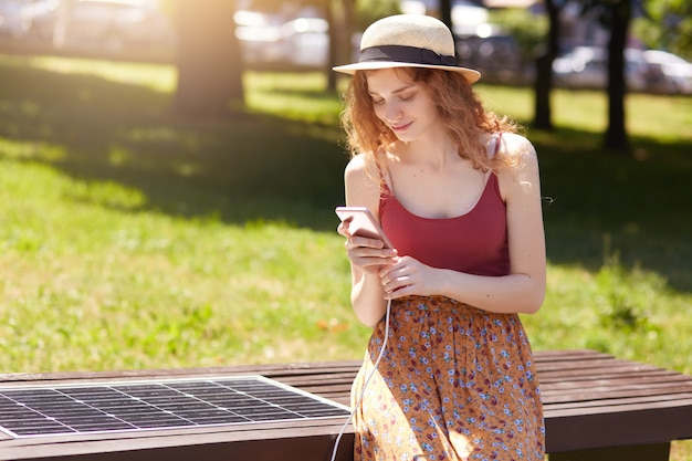 Horizontal short of young girl charges mobile phone via usb outdoors, lady sits on bench with solar panel in town park. public charging on city street. modern technology, ecology, alternative energy.