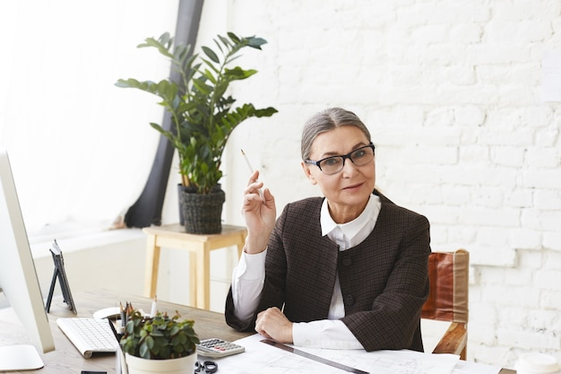 Horizontal shot of 50 year old woman architect in formal wear holding pencil while doing paperwork in light office, checking technical drawings, having serious expression. architecture and engineering