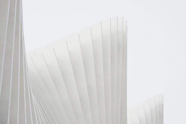 Горизонтальная съемка абстрактных зданий с белыми металлическими ребрами и стеклянными окнами