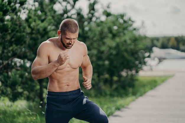 Horizontal shot of active bearded man has active exercises outdoor