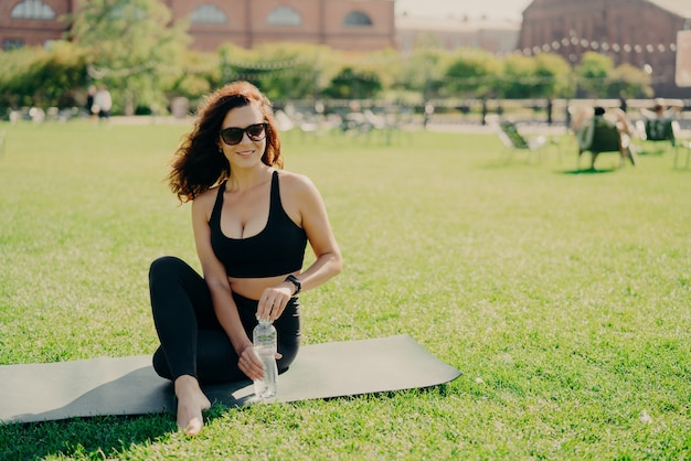 Horizontal shot of active slim woman in sportswear sits on karemat holds bottle of cold water has rest after exercising abdominal muscles poses on green lawn wears sunglasses. workout at street