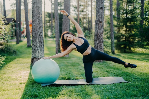 Horizontal shot of active slim woman with cheerful expression leans aside does exercises with fitness ball, dressed in sportsclothes, poses outdoor against tall trees on karemat. healthy lifestyle