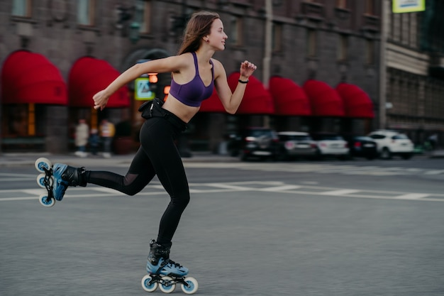 Horizontal shot of active slim young woman rides fast on rollerskates improves balance agility and coordination dressed in cropped top and leggings poses on street road focused into distance