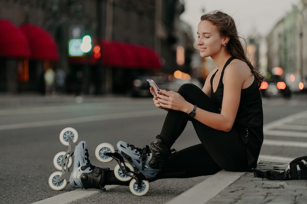 Horizontal shot of active sporty woman dressed in sportsclothes wears rollerblades focused at smartphone enjoys inline skating outdoors leads active lifestyle. rollerskating as hobby concept