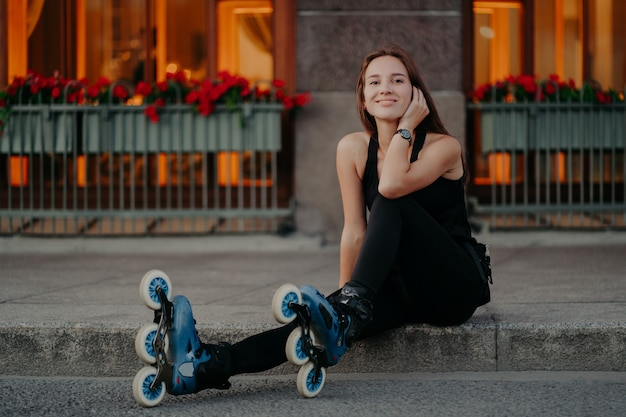 Horizontal shot of active young woman takes break while riding rollers at street dressed in black sportsclothes feels satisfied smiles pleasantly poses outdoor. summer lifestyle and rest concept