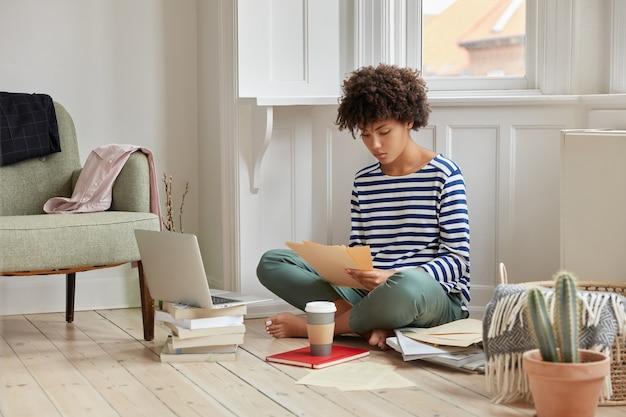 Inquadratura orizzontale della mangiatoia amministrativa si siede nella posa del loto sul pavimento, contratto di studi