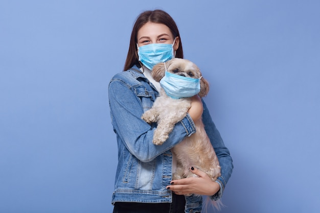 Horizontal shot of adult woman wearing medical protected face mask, female holding dog with mask also in hands, posing isolated on lilac wall. coronavirus, covid 19, disease, pandemic concept.