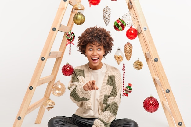 Horizontal shot of amazed happy young woman with afro hair points at camera has glad expression sees awesome thing in front wears casual sweater sits on floor