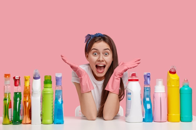 Horizontal shot of amazed overjoyed woman spreads hands, wears protective gloves, sits at table with many detergents