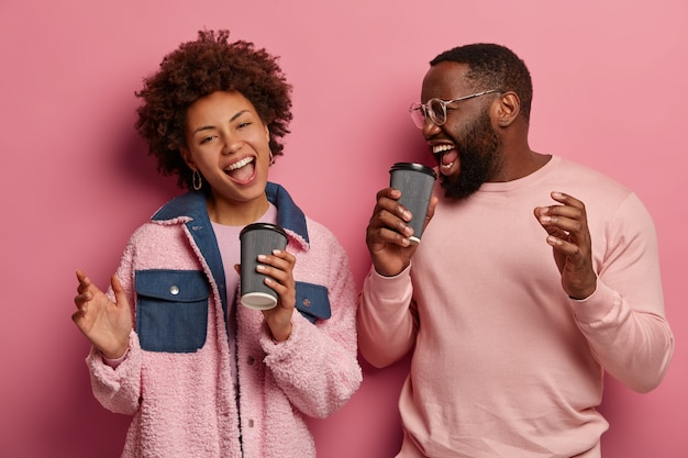 Horizontal shot of amused cheerful woman and man with dark skin have fun during coffee break, sing song along, dance carefree