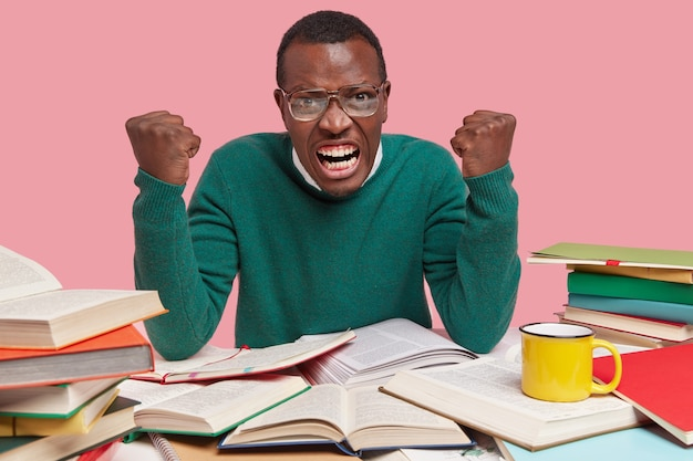 Horizontal shot of angry annoyed furious black scientific worker clenches fists and teeth with irriatation, poses at workplace with piles of books