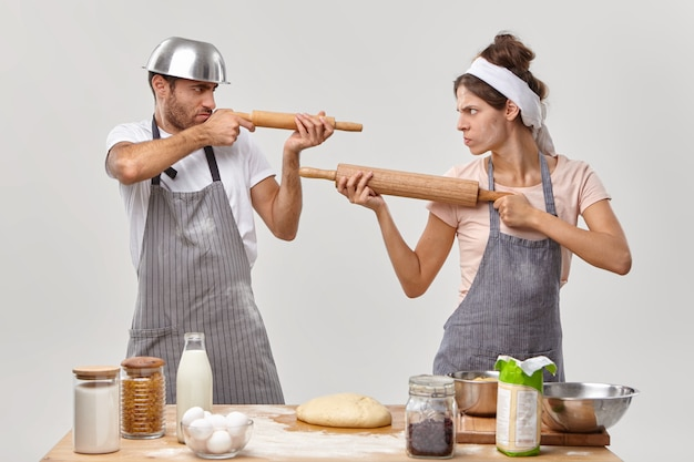 Horizontal shot of angry husband and wife feel like opponents, shoot at each other with rolling pins, cook together at home, make dough with flour, prepare delicious pastry, do bakery. kitchen fight