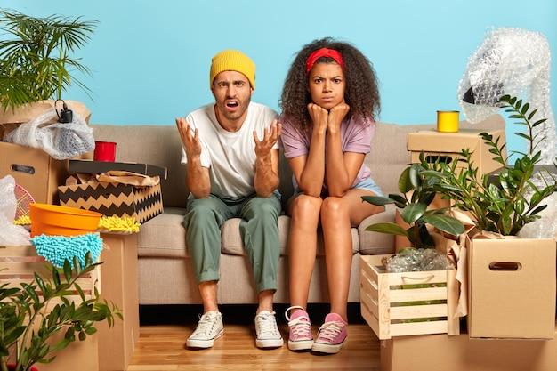 Inquadratura orizzontale di giovani coppie infastidite che si siedono sul divano circondato da scatole